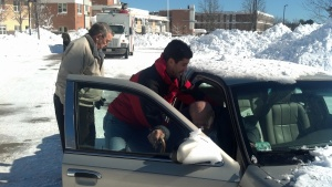 ARCEM CEO Jarrett Barrios helps Bill Hearns of North Weymouth at the Weymouth High School Shelter today.