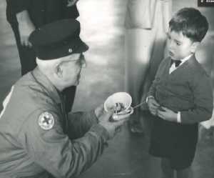 An American Red Cross volunteer helps a young boy at a shelter.